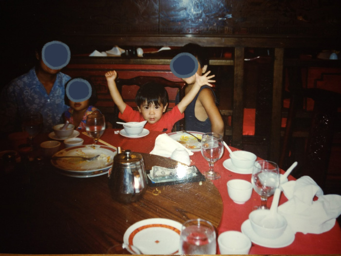 Marina as a child, in a restaurant with family. Marina spreads their arms wide dramatically.