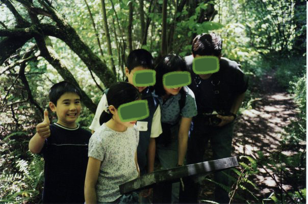 Marina as a kid, in a forest with family. Marina gives a big grin and thumbs up, while the rest of the family pretends to read a sign.