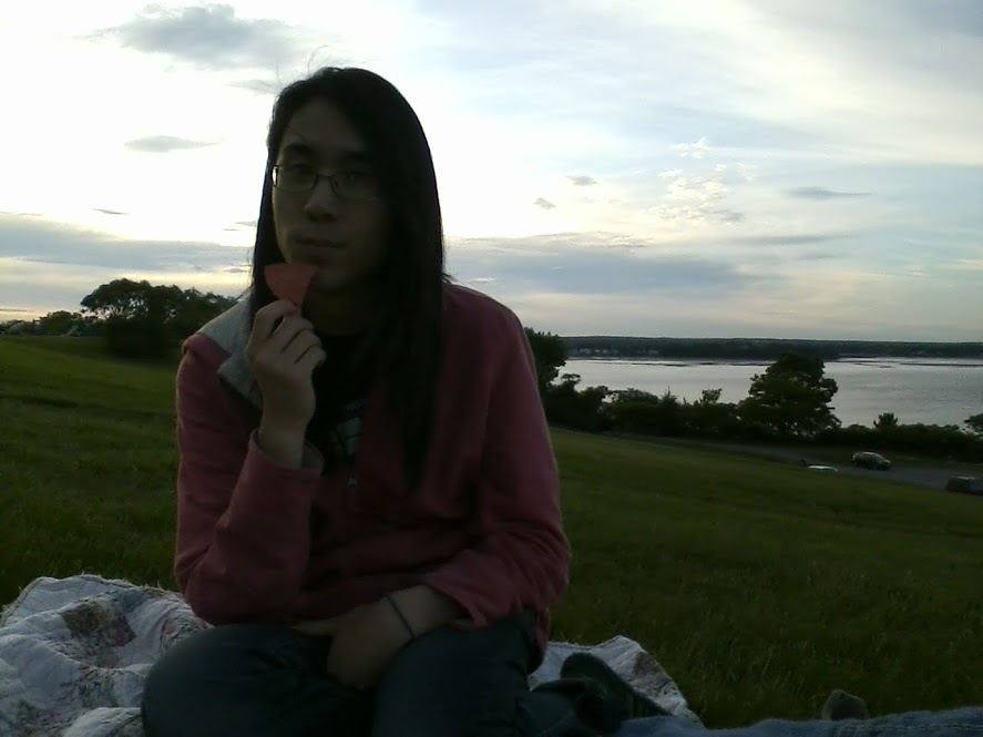 Marina sitting on a grassy hill, eating a chip in the waning light.