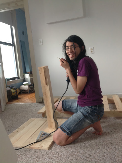 Marina stands next to a partly assembled bed with a drill.