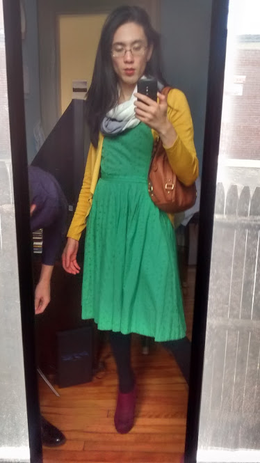 Another selfie of Marina's outfit. She's wearing a green dress with a mustard yellow cardigan and a white and grey scarf.