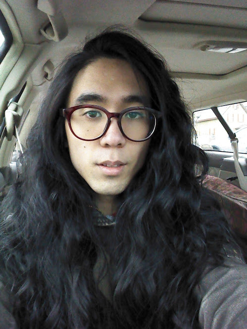 Marina sitting in a car with dramatic wavy hair (from taking out a french braid after leaving it in for several days)