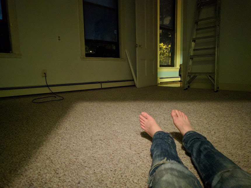 Marina's legs/feet on the ground in her empty apartment.