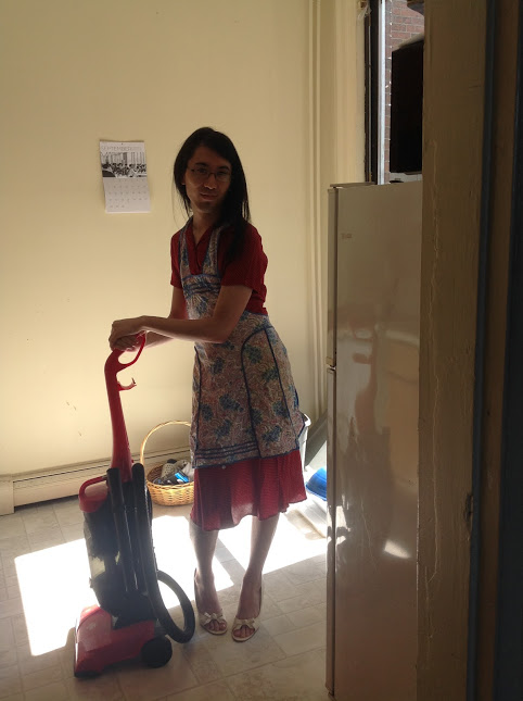 Marina wears an ironically 1950s housewife-esque outfit while pretending to vacuum.